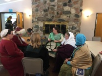 A Bardic Storm pickup session at Kingdom Twelfth Night 2017: second from left, me, in furry hat; then Pat Savelli, with guitar; Finn, with bodhran; and Halle in white scarf.
